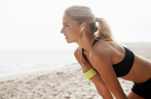 Attractive female jogger taking a rest after a run on the beach